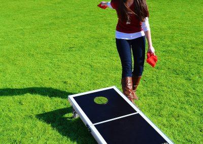 Young Woman Playing Cornhole-Bean-Bag-Toss-Yard-Game